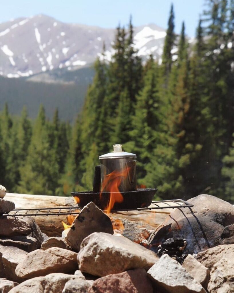 Coffee percolating atop a campfire grill grate with mountains and trees in the distance.