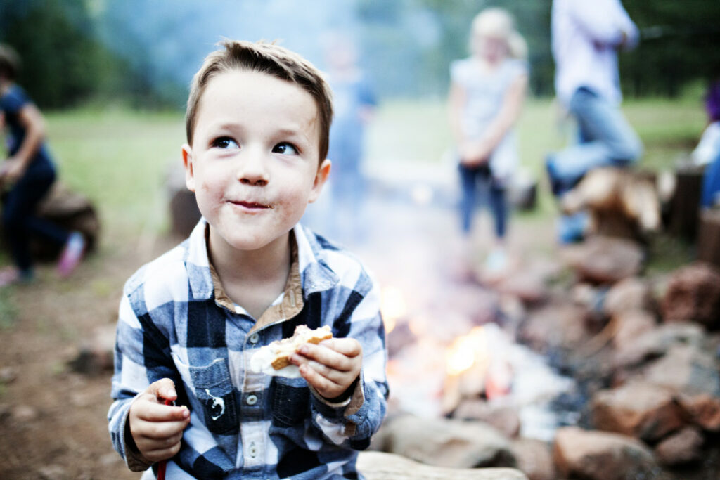 Young, happy boy outside eating a smore with family and campfire in the background behind him.