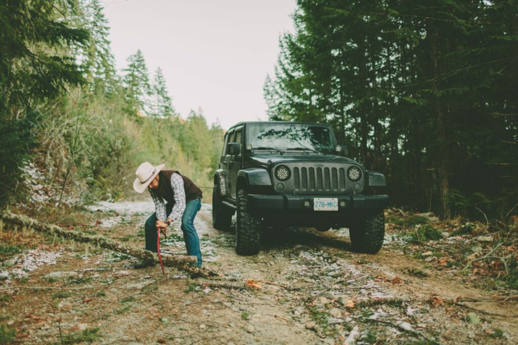 A man chopping a tree that has fallen in the dirt road. Hard labor can lead to workamping regrets.