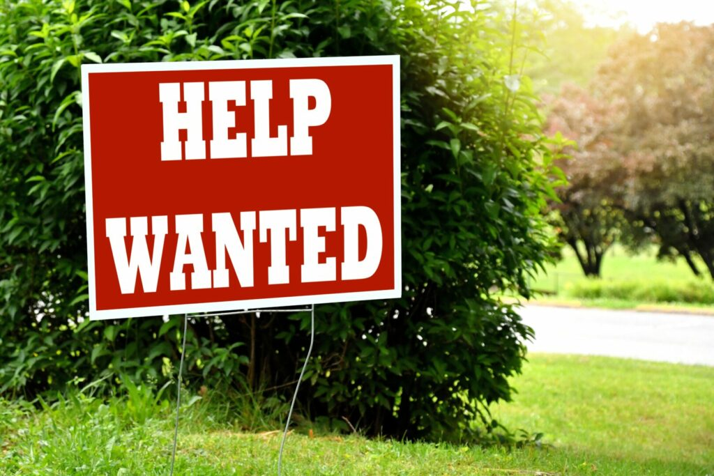 A help wanted sign on a lawn