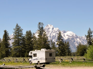 A lone RV is boondocking on open land in Wyoming with mountains and trees in the background.