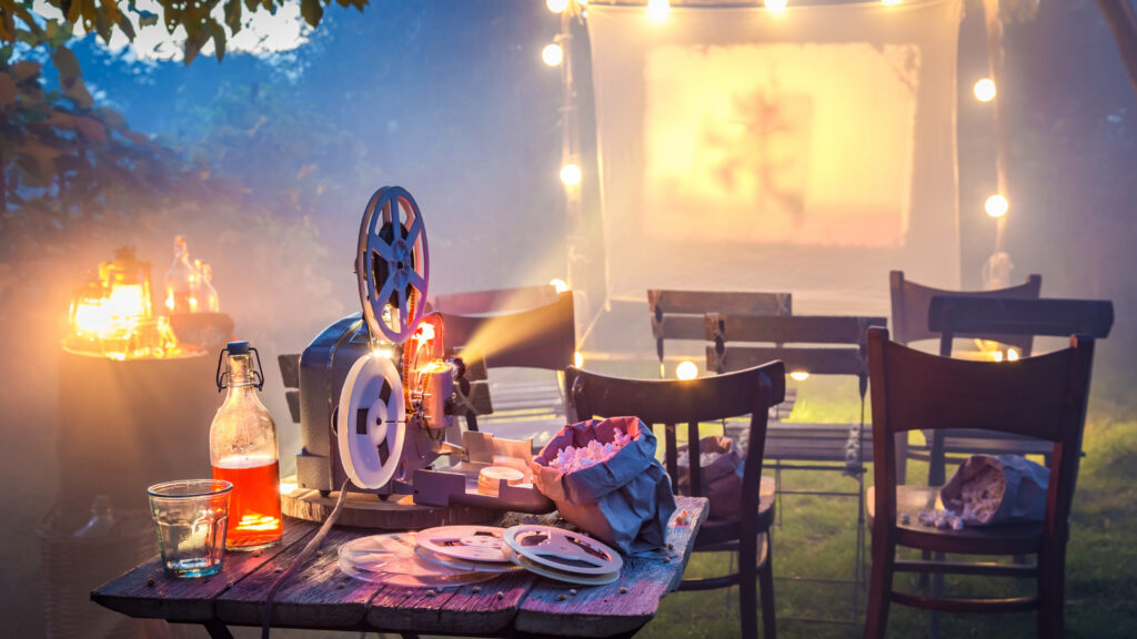 A backyard movie projector lights up a screen with snacks and drinks on the projector table and empty chairs for the movie.