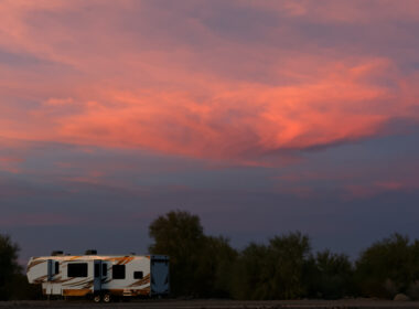A fifth wheel RV is longterm boondocking in a desert with a pink sunset in the sky.