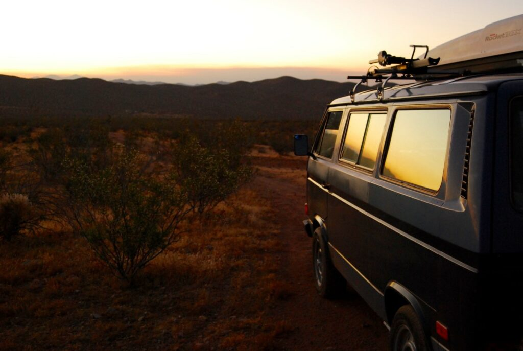 A van free camping in Arizona desert with the sunsetting over the mountains in the distance