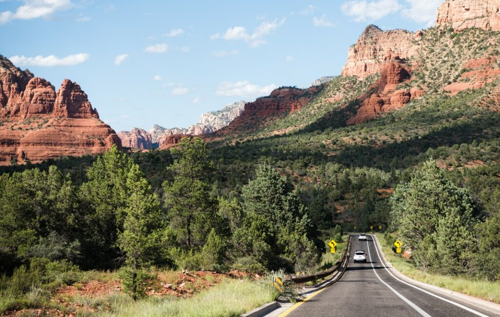 Vehicle traveling down a road through the red mountains of Sedona, Arizona.