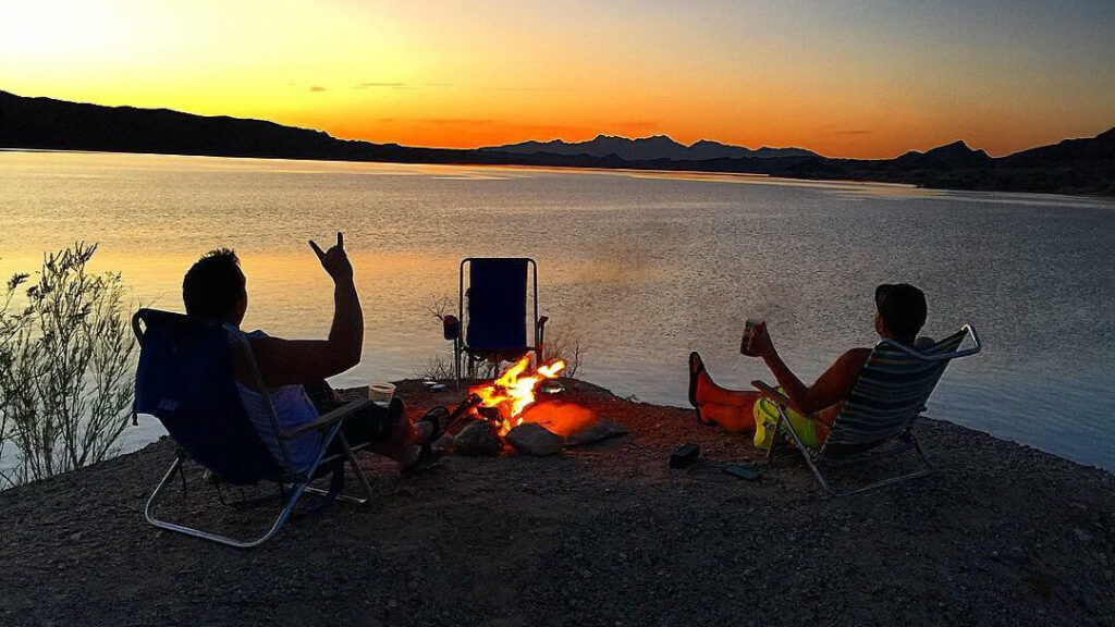 Two campers relax in chair next to a fire on the beach of Lake Havasu while enjoying the sunset.