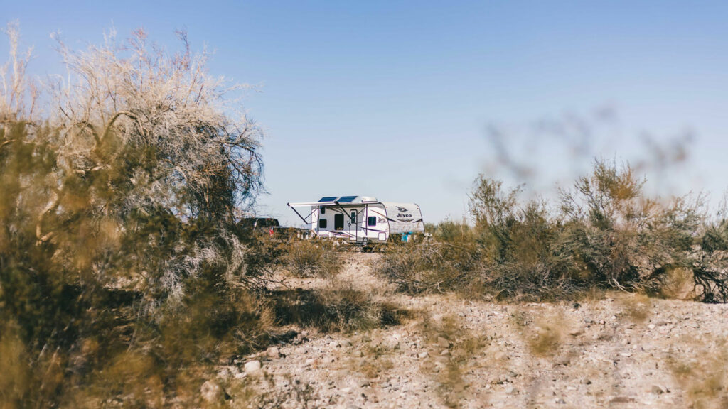 A recreational vehicle free camping in Arizona in the deserts of quartzsite surrounded by plants in the middle of a sunny day.