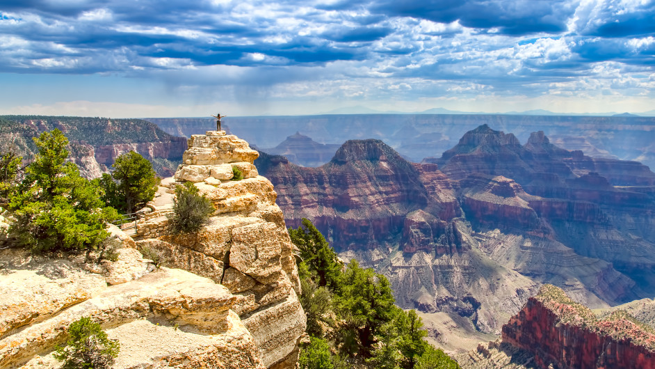 A hiker stands a a tall rock ledge in the distance with a landscape of striped mountains and canyons surrounding her