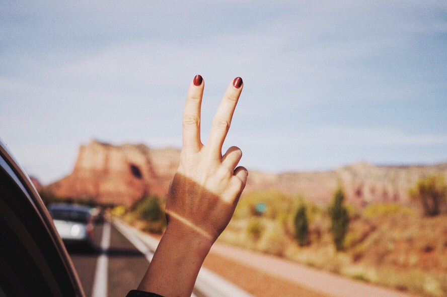 A car passenger gives the peace sign out the window while driving through the desert in Arizona