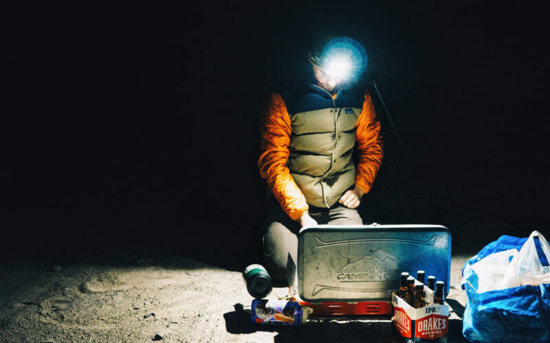 A headlamp is one of many boondocking must-haves and it cuts through the blackness of night as a camper kneels by his stove.
