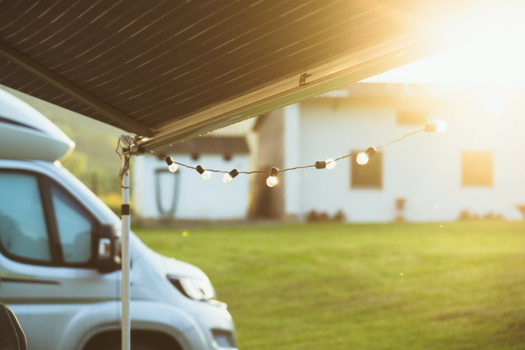 Outdoor LED lightbulbs strung along a camp awning next to a van with the sun streaming towards the camera.