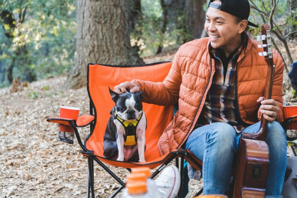 Man and his boston terrier happily sit on orange camp chairs while relaxing in the woods.