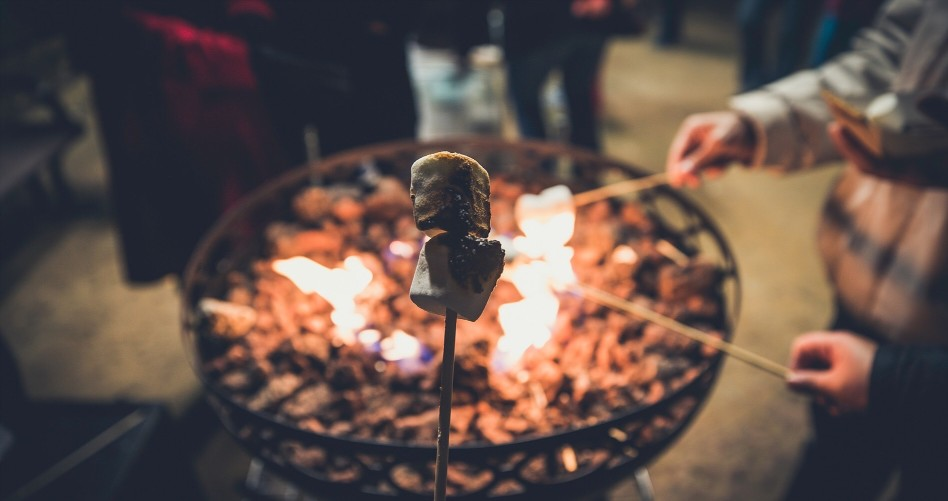 A close up of marshmallows on a stick being roasted over a fire.