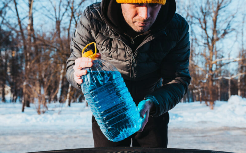 Man outside in cold weather prepares to pour blue antifreeze from a RV winterizing kit