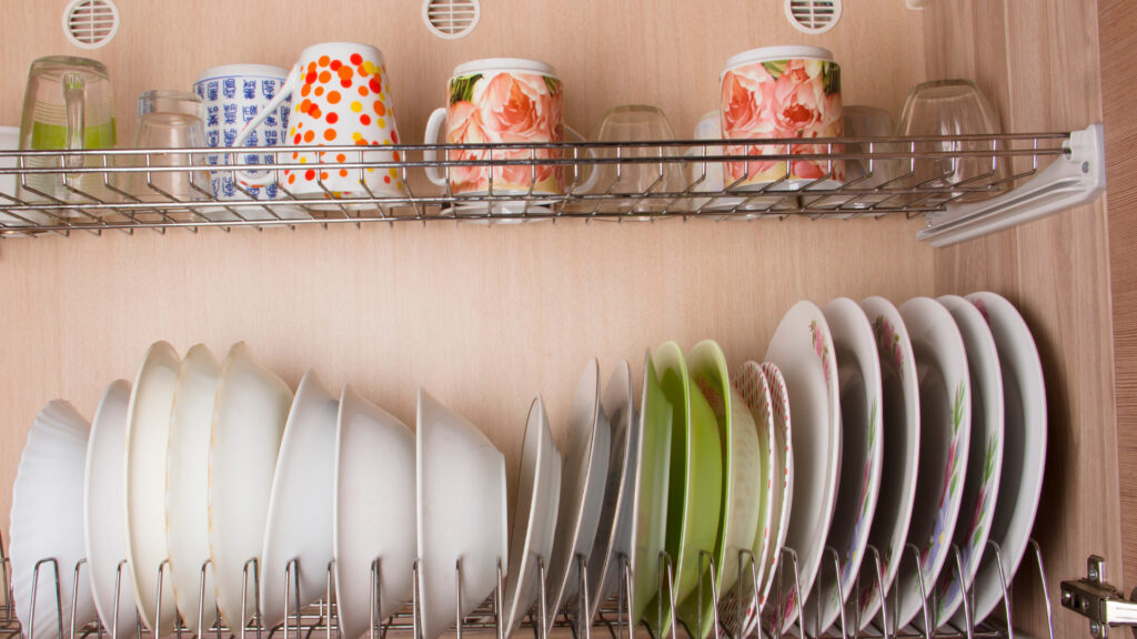 Dish cradles keep plates and bowls organized in an RV pantry.