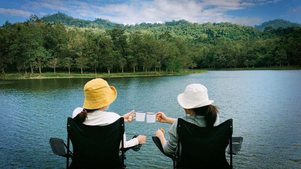 Two friends drinking camping cocktails while sitting in chairs outside beside a lake