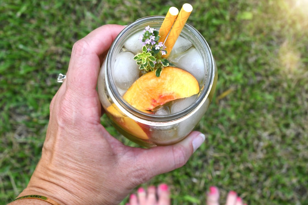 A woman holding a peach cocktail drink.