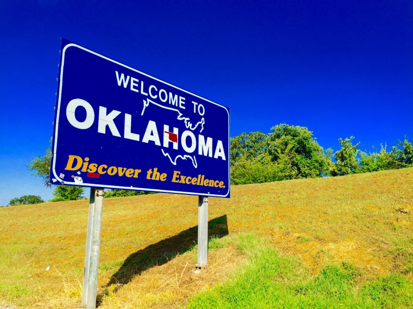 A blue road sign welcoming drivers to the state of Oklahoma.