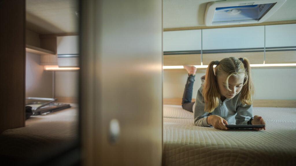 A young girl with pigtails plays on her tablet while lying on the bed in an RV.