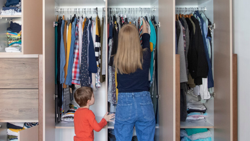 A woman organizes a cluttered closet with her son by her side.