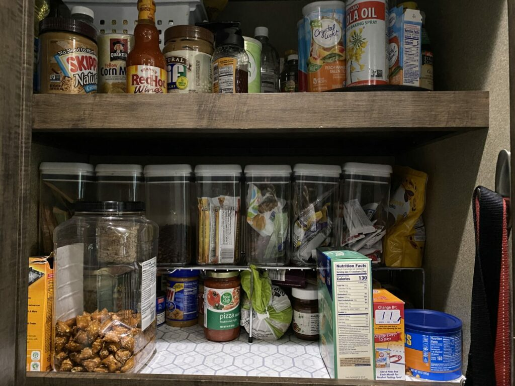 An RV pantry is organized chaos with snacks stored in matching pantry bins.
