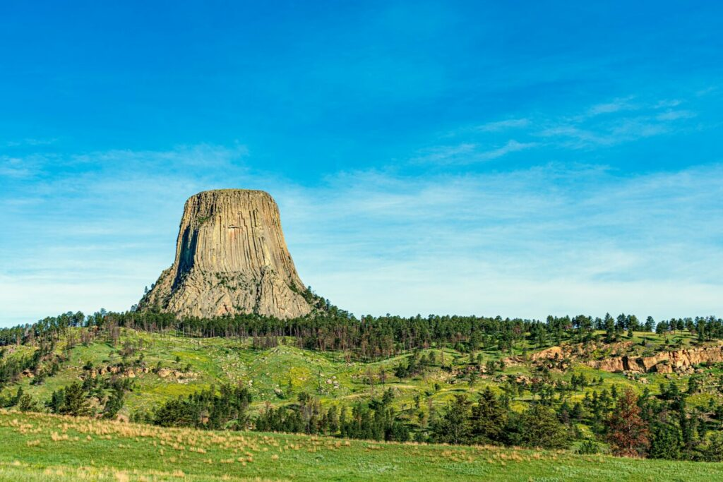 Green fields and blue sky surround the towering Devil's Tower National Monument