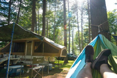 Shot of feet in a hammock with pop up camper in the background and the sun streaming through the trees