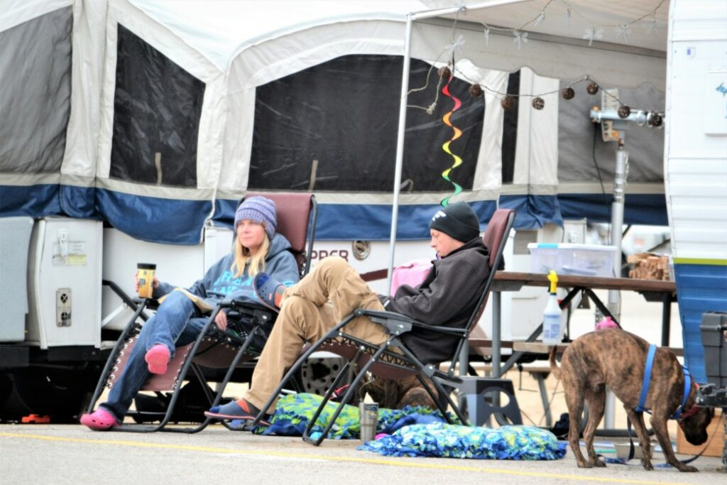 Man and woman sit in camp chairs on a cold day contemplating if they have any Pop-Up camper regrets