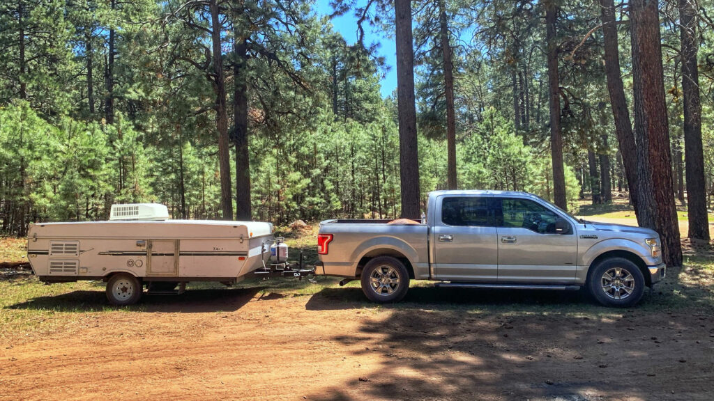 Ford F 150 pulling a pop up trailer into a wooded campground with a dirt road.