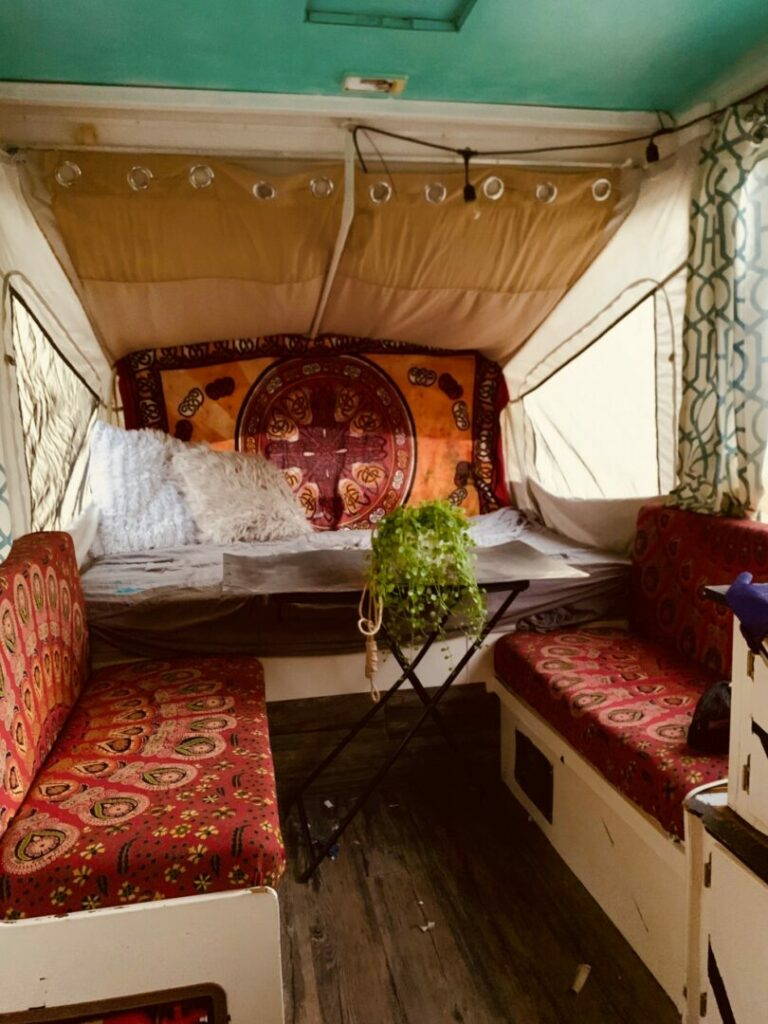 Inside of a remodeled pop-up camper with boho vibes and new red upholstery.