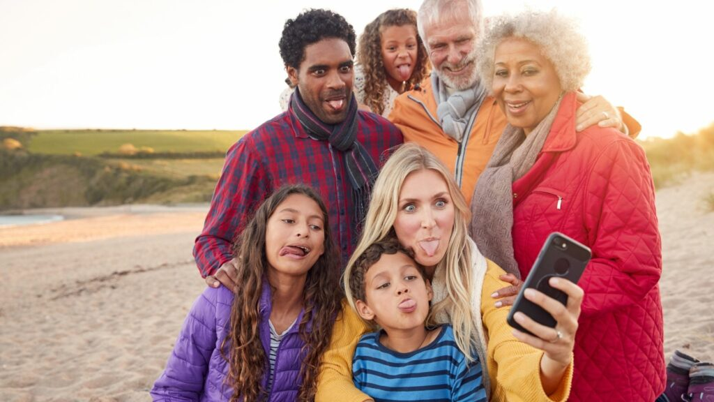 Multi-generational family takes a goofy photo on the beach while on their camping trip.