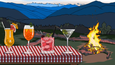 Camping cocktails sitting on a picnic table with a campfire in the background