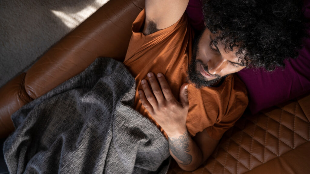 Man with dark curly hair sleeping on couch in a motorhome.