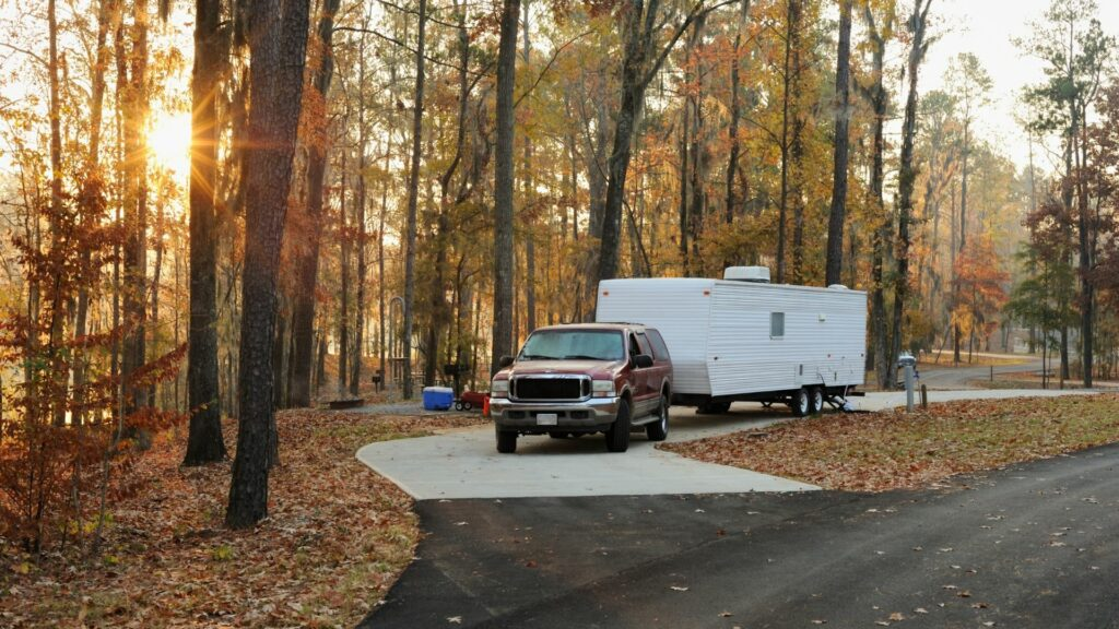 Pull-through campsite surrounded by autumn trees has a truck and travel trailer set up for the weekend as the sun rises.