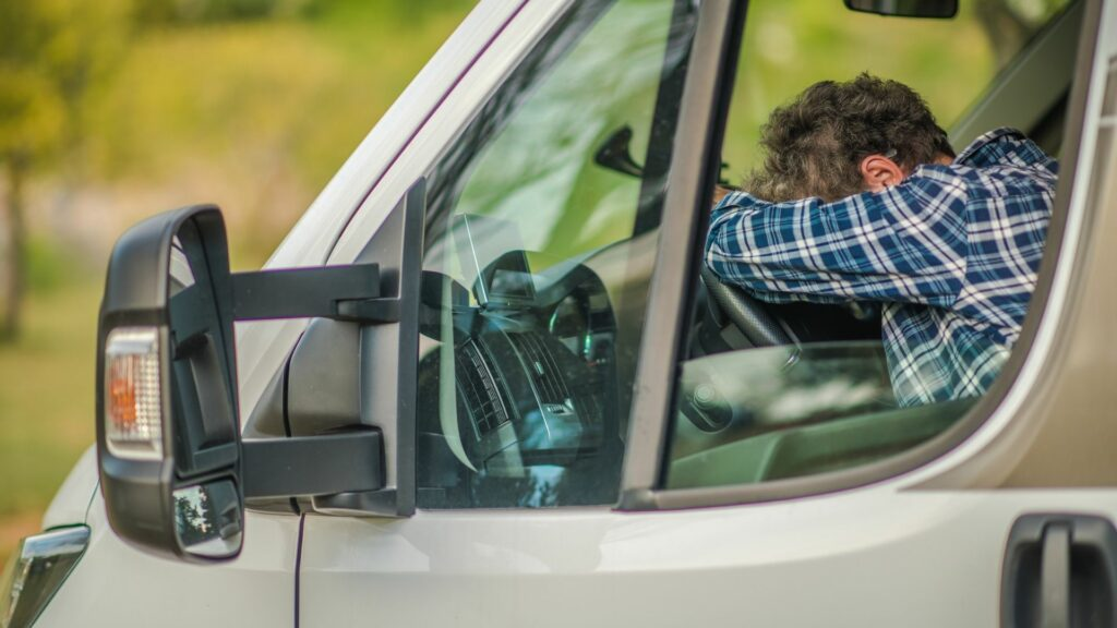 Frustrated woman puts her head on the steering wheel of an RV.