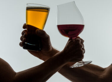 Beer and Wine glasses in hands of wrestling arms.