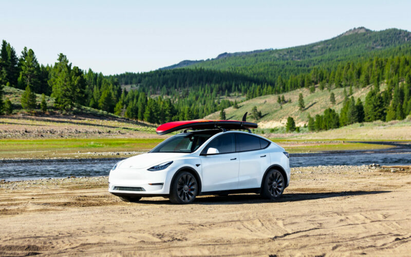 a Tesla Model Y parked in the sand with water and mountains behind it