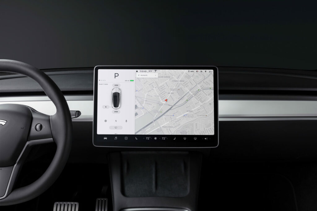 Interior shot of a Tesla Y Model showing the screen and steering wheel