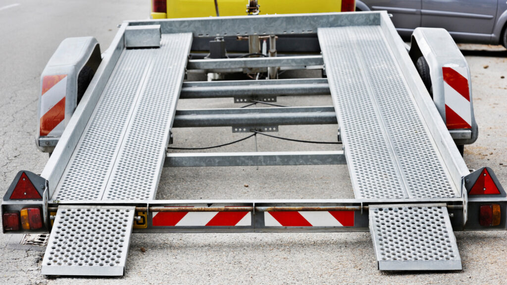 A flatbed trailer with the ramp down ready for a car to load