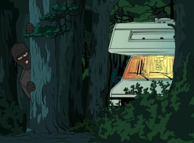 A burglar hiding in the dark forest behind a tree with a lit up RV parked nearby.