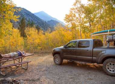 A camper naps on a picnic table while camping in the autumn forest in California with his truck and surfboard.