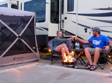 A couple cheers outside there RV while sitting in camping chairs and surrounded by fun RV accessories.