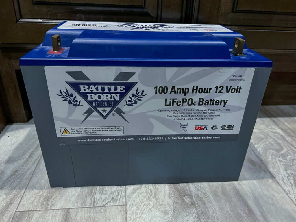 An RV battery is safely stored for the winter inside the house.