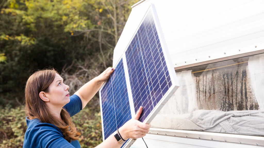 A woman installs a solar panel to her RV to help her keep her RV batteries charged.