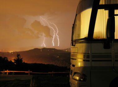 Motorhome in campground at night with lightning storm in background