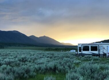 An instagrammable view of RVs parked in a beautiful grassy field set against mountains with a golden glow to the sunrise.