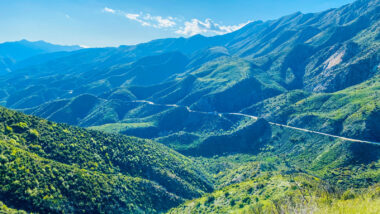 Aerial view of a road winding through the mountains of Los Padres National Forest.