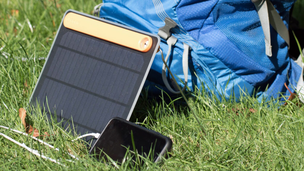 Portable solar panels charging a smartphone next to a hiking pack.