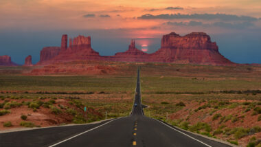 A sunset over Monument Valley with wide open roads.