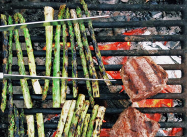 Top-down view of asparagus and steaks cooking on a campfire grill grate